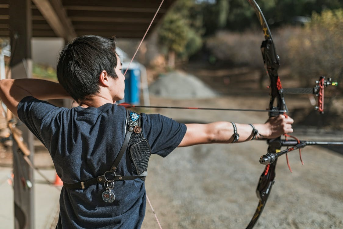 Man shooting compound bow and arrow