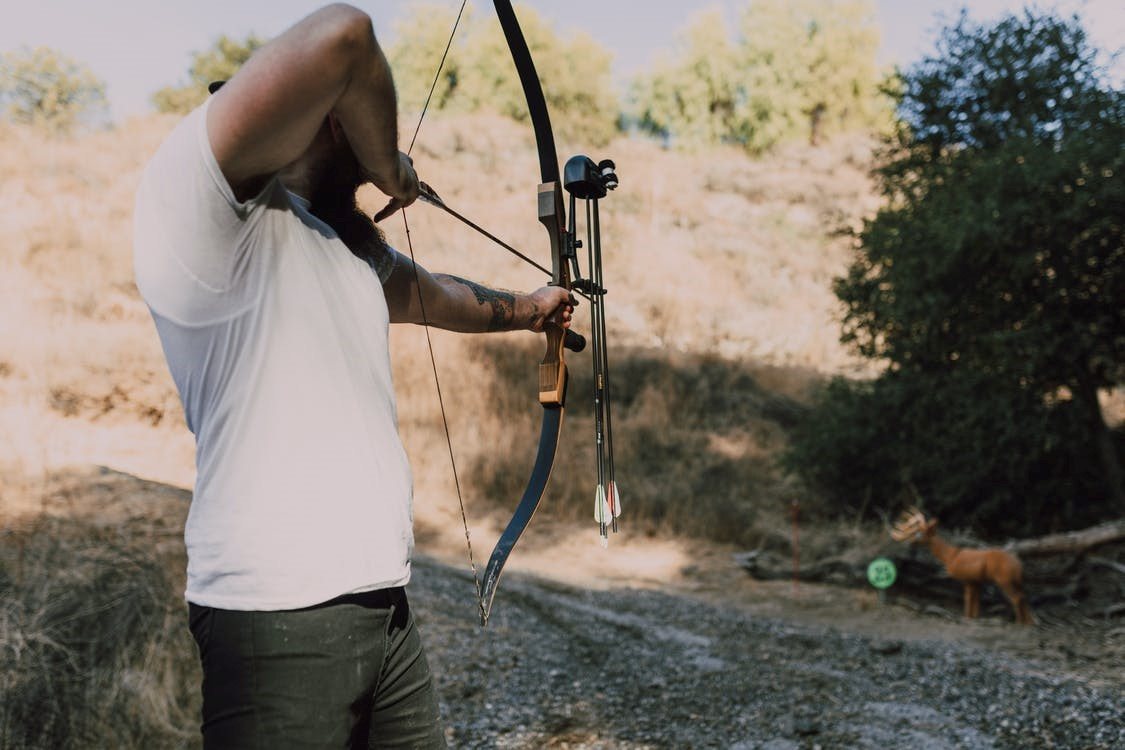 man hunting with bow